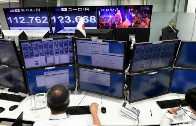 Des courtiers suivent à la télévision la retransmission de l'élection d'Emmanuel Macron à la présidence de la République à la Bourse de Tokyo, le 8 mai 2017 ( AFP / Toshifumi KITAMURA )