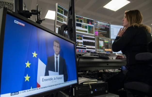 Les marchés financiers, dont la Bourse de Paris, évoluent sans enthousiasme au lendement de la victoire d'Emmanuel Macron. Ci-contre des courtiers à Londres écoutent le discours d'Emmanuel Macron après son élection de dimanche ( AFP / CHRIS J RATCLIFFE )